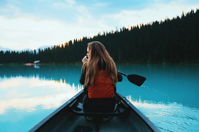 A girl sitting on a canoeing boat with a life jacket holding a canoe