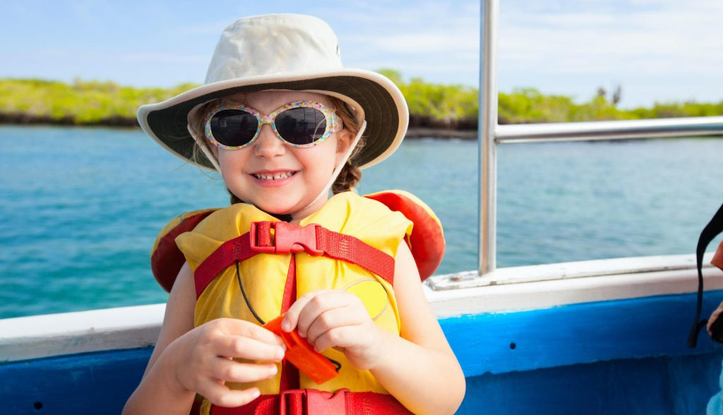 Toddler wearing a life jacket and smiling