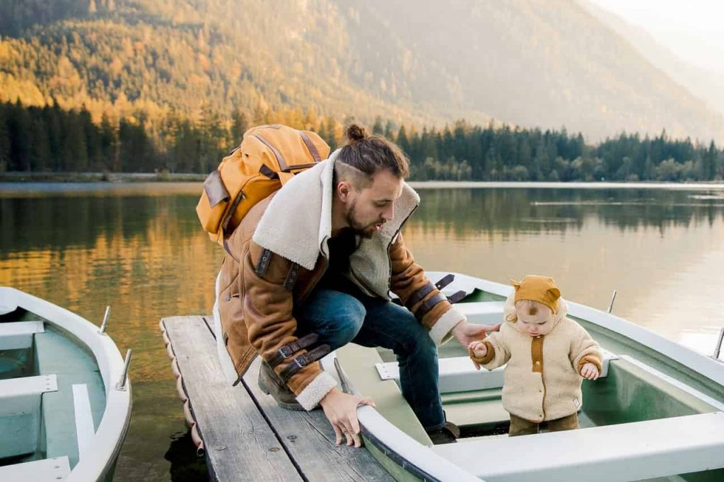 Picture of a toddler with his father in a boat without a life jacket