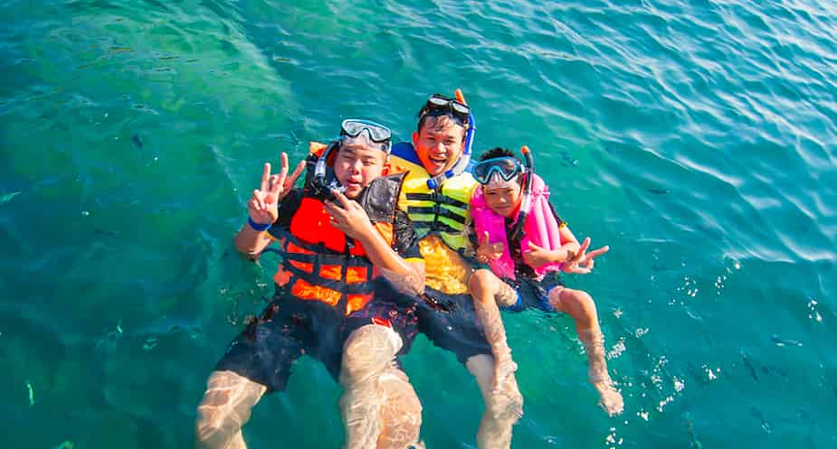 Three people wearing snorkeling life jacket in the ocean