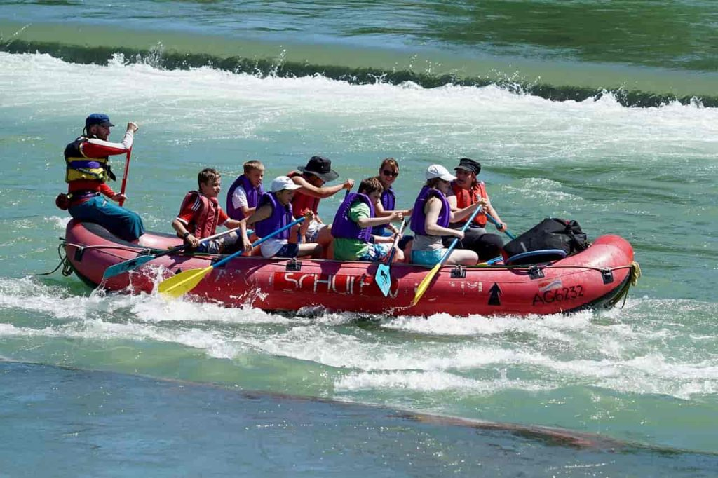 people rafting in white water wearing life jacket