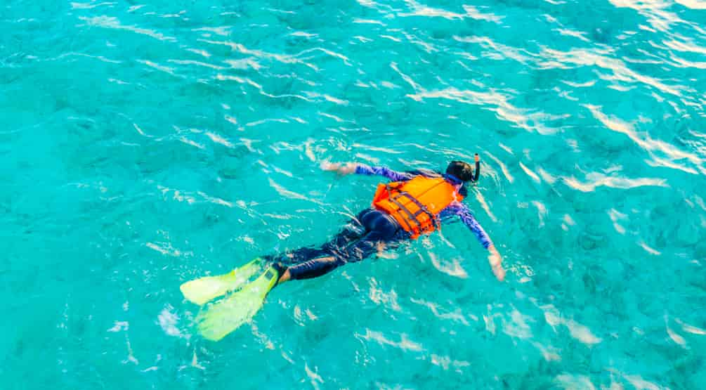 person snorkeling in ocean wearing snorkeling life jacket
